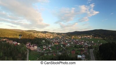 Rising up over a small town in the forest valley situated on...