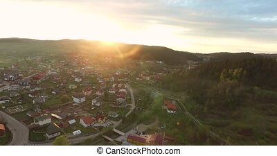 Panoramic shooting sunrise over small town in a wooded valley