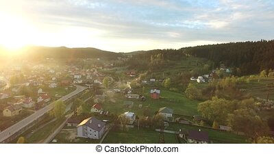 Sun rays illuminate a small village. Aerial view - Sun rays...