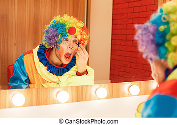 Clown does a make-up in front of the mirror. - Cheerful...