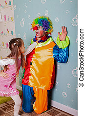 Cruel girl playing with scared clown