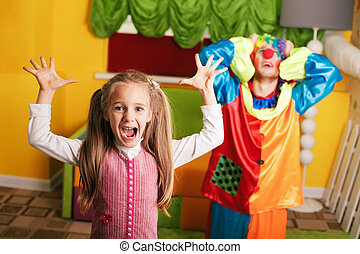 Little girl plays with upset clown.