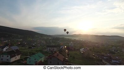 Two balloons are flying to meet the sunset. Aerial view