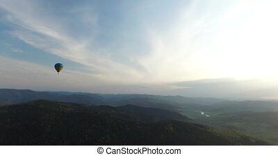 Large balloon flies over a beautiful forest scenery. Aerial...