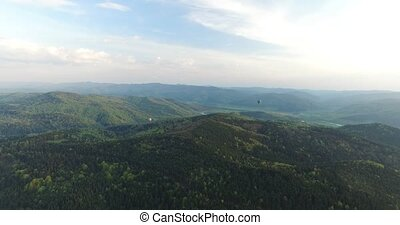 Aerial. In the distance two balloons fly over the forest -...