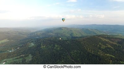 Two aerostat flying at different heights above the forest,...