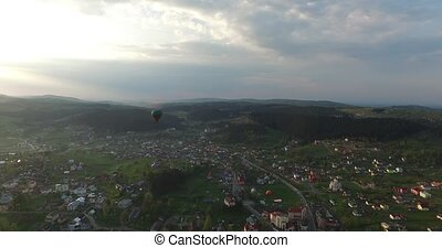 Above the small town is flying balloon. Aerial view