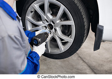 car mechanic screwing or unscrewing  wheel of lifted automobile by pneumatic wrench at repair service station