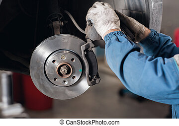 change the old drive to the Brand new brake disc on car in a garage. Auto mechanic repairing .