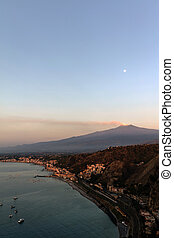 Mount Etna and the Giardini Naxos coastline at dawn. View...