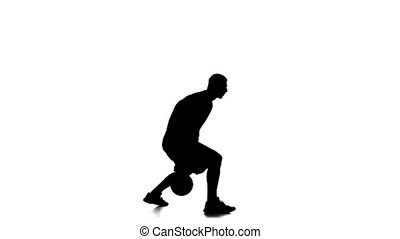 Basketball player fills the ball by hand. Side view. White background