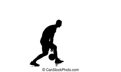 Basketball player fills the ball by hand. Side view. White...