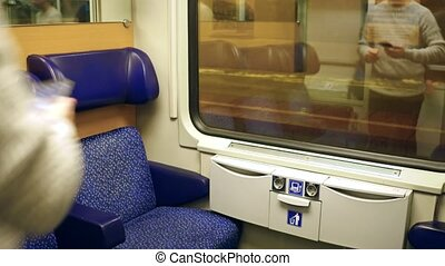 Man in sweater taking his seat in a train and using his...