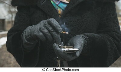 Woman dressed in black gloves holds a ashtray