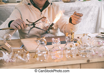 Craftsman decorating glass objects with a torch.