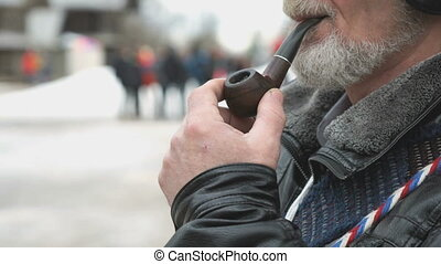 Adult man with a beard smokes using a smoking pipe. Man...