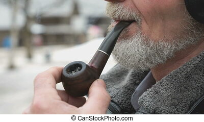 Adult man holding a wooden pipe in his hands because he...