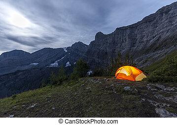 Illuminated tent camping on ridgeline of mountain -...