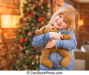 Girl Holding Teddy Bear In Front of Decorated Christmas Tree