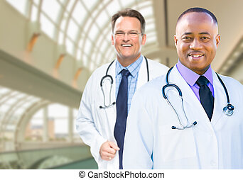 African American and Caucasian Male Doctors Inside Hospital...