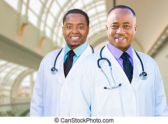Two African American Male Doctors Inside Hospital Office -...