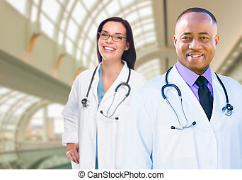 Female and Male Caucasian and African American Doctors in...