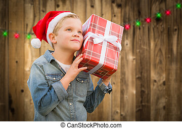 Curious Boy Wearing Santa Hat Holding Christmas Gift On Wood