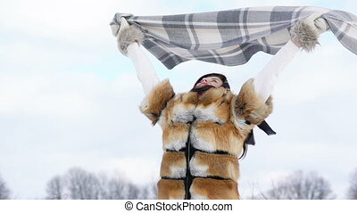 Happy girl raising and covered in plaid in winter day....