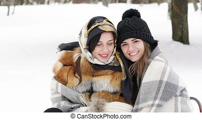 Two girls covered in plaid embracing and smiling in the...