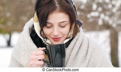 Young girl drinking hot tea in winter day. Slowly