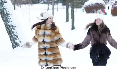 Two pretty girls running through the snow in park. Slowly