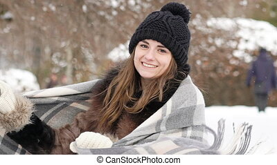 Portrait of pretty girl smiling to the camera in windy cold day. Slowly