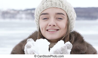Beautiful happy girl blowing snow outdoor. Slowly.