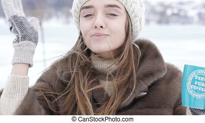Pretty girl drinking a cup of hot beverage outdoor in winter...