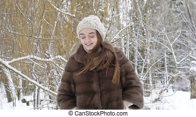 Happy smiling girl walking and looking back in the park in...