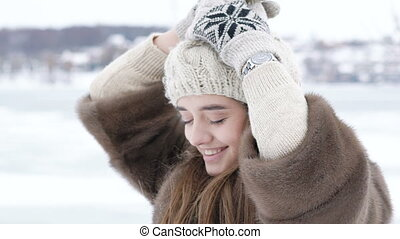 Pretty girl correcting and posing with hat in winter day....