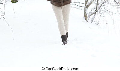 Pretty girl walking in the park in snow-white day. Slowly.
