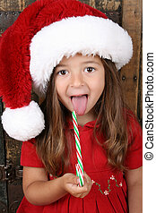Christmas candy - Cute brunette girl eating Christmas candy...