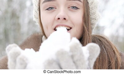 Close up portrait of beautiful happy girl blowing snow...