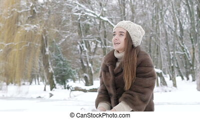 Happy young girl throwing up snow and laughing in the park. Slowly