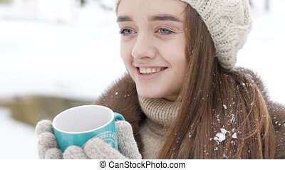 Pretty girl holds a cup of hot beverage in cold winter day....