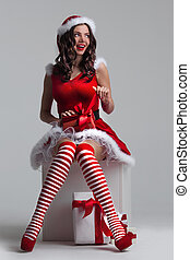 Girl unwrapping christmas present - Beautiful young pin-up...