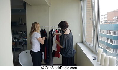 Two women choose blue dress from rack with hangers in flat....