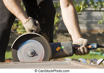 Closeup of worker hands with angle grinder