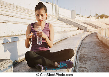 Woman relaxing after sports and drinking water.