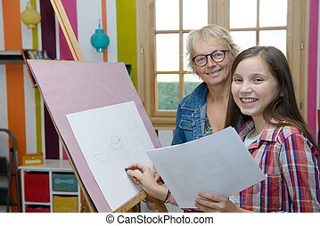 young teen girl drawing with her teacher