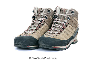Old scuffed hiking boots on white background