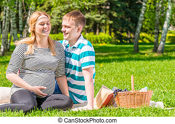 European family at a picnic in the park, woman is pregnant