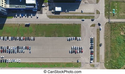 Aerial survey of parking lot near the factory, around which...