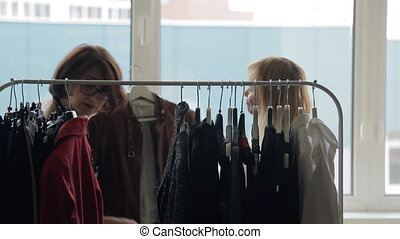 Two women discuss fashion trends, view clothes on rack with...